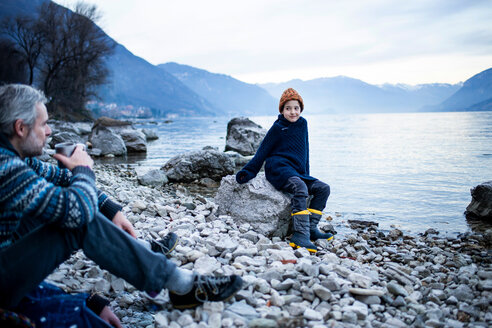 Father and son on lakeside, Onno, Lombardy, Italy - CUF49232