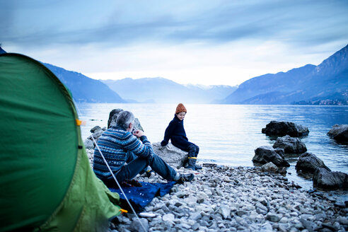 Father and son camping by lakeside, Onno, Lombardy, Italy - CUF49235