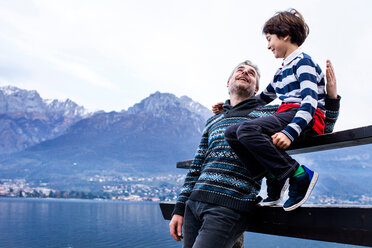 Boy and father sitting on pier fence, Lake Como. Onno, Lombardy, Italy - CUF49253