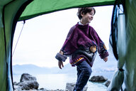 Boy playing outside tent on lakeside, Lake Como, Onno, Lombardy, Italy - CUF49256
