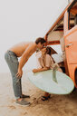 Young surfing couple kissing by recreational vehicle on beach,  Jalama, Ventura, California, USA - ISF20517