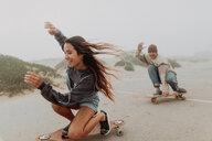 Young couple skateboarding in misty beach carpark, Jalama, California, USA - ISF20553