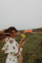 Young woman with wildflowers dancing at coast,  Jalama, California, USA - ISF20559