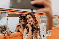 Young couple on road trip in recreational vehicle taking smartphone selfie,  portrait, Jalama, California, USA - ISF20562