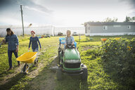 Farmers with wheelbarrow and tractor on sunny farm - HEROF20702