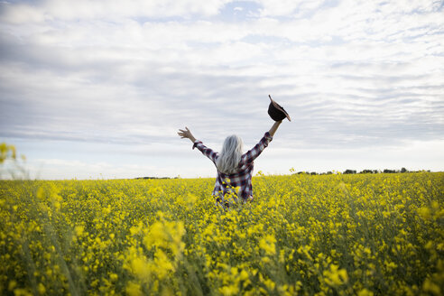 Exuberant woman with arms outstretched in  idyllic, yellow rapeseed crop field on farm - HEROF20705