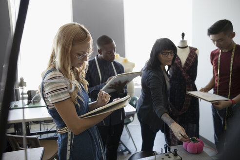 Fashion design instructor and students taking notes and pinning fabric on dressmakers model in studio - HEROF20747