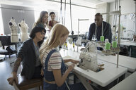 Fashion design instructor and students using serger in studio - HEROF20759
