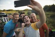 Enthusiastic male friends with camera phone taking selfie - HEROF20780