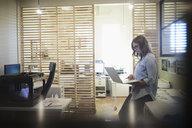 Female designer using laptop near 3D printer in office - HEROF20786