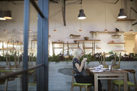 Female cafe business owner paying bills, working at laptop - HEROF20819