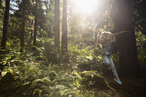 Exuberant girl jumping off rock in sunny woods below trees - HEROF20855