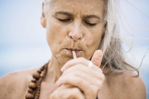Portrait of senior hippie woman smoking outdoors - SBOF01701