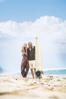 Senior hippie couple standing with surfboard on the beach - SBOF01707