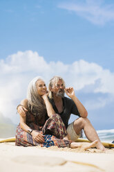 Portrait of senior hippie couple relaxing on the beach - SBOF01710