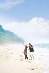 Happy senior hippie couple with guitar dancing on the beach - SBOF01713