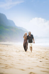 Senior hippie couple strolling together on the beach - SBOF01719