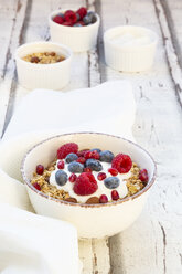 Bowl of muesli with Greek yogurt, popped quinoa, raspberries, blueberries and pomegranate seed - LVF07768