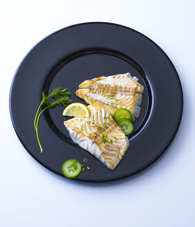 Redfish fillet on black plate garnished with herbs - PPXF00166