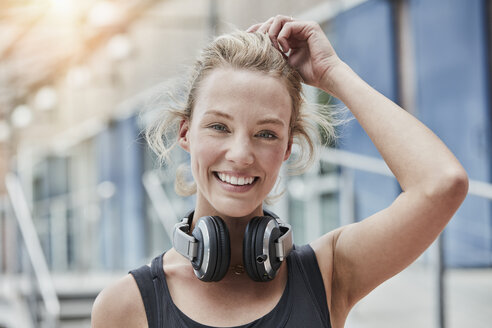 Portrait of smiling young woman with headphones - RORF01718