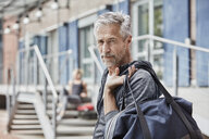 Portrait of mature man with sports bag in front of gym - RORF01721