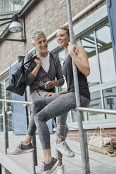 Portrait of mature man with sports bag and laughing young woman in front of gym - RORF01724