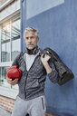 Portrait of mature man with headphones, sports bag and red boxing gloves standing in front of gym - RORF01730