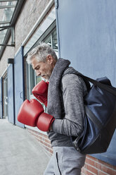 Mature man with towel, sports bag and red boxing gloves standing in front of gym - RORF01733
