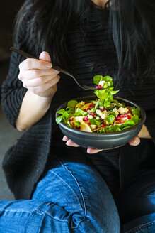Woman eating mixed salad with lamb's lettuce, feta, pear, pomegranate seed and walnuts - SARF04106