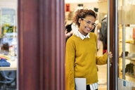 Young woman standing in door of a fashion store, holding laptop - PESF01395