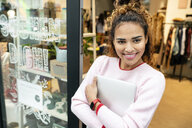 Young woman standing in door of a fashion store, holding laptop - PESF01407