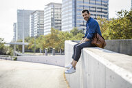 Smiling man with leather bag sitting on wall - GIOF05722
