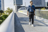 Man with headphones and coffee to go walking on a footbridge - GIOF05725