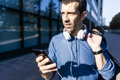 Portrait of man with headphones, bag and mobile phone looking at distance - GIOF05740