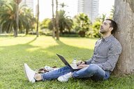 Man with laptop leaning against tree trunk on meadow in city park relaxing - GIOF05755