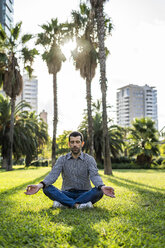 Man sitting on meadow in city park doing yoga exercise - GIOF05764