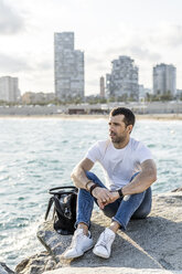 Spain, Barcelona, man sitting on a rock in front of the sea looking at distance - GIOF05767