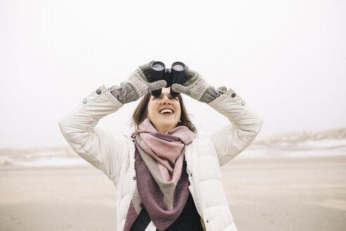 Laughing woman using binoculars on the beach looking up - KMKF00753