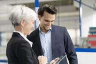 Smiling businessman and senior businesswoman with tablet talking in a factory - DIGF05636
