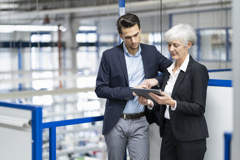 Businessman and senior businesswoman with tablet talking in a factory - DIGF05639