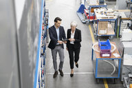 Businessman and senior businesswoman with tablet walking in a factory - DIGF05645