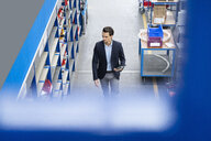 Businessman with tablet walking in a factory - DIGF05651