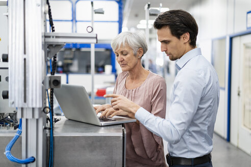 Businessman and senior businesswoman working on laptop in a factory - DIGF05657