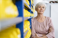 Portrait of confident senior woman in storehouse of a factory - DIGF05669