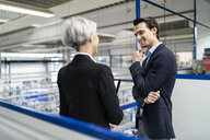 Smiling businessman and senior businesswoman with tablet talking in a factory - DIGF05678
