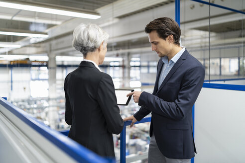 Businessman and senior businesswoman with tablet talking in a factory - DIGF05681