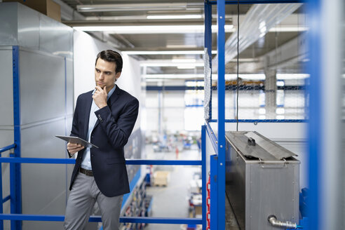 Thoughtful businessman with tablet in a factory - DIGF05687