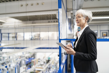 Senior businesswoman using tablet in a factory - DIGF05699