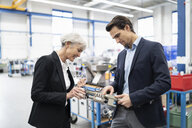Businessman and senior businesswoman examining workpiece in a factory - DIGF05702