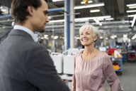 Smiling senior businesswoman and businessman talking in a factory - DIGF05720